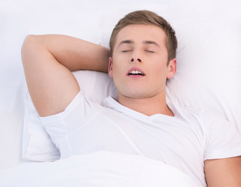 Man lying on his back in bed and sleeping with mouth slightly open to imply snoring.
