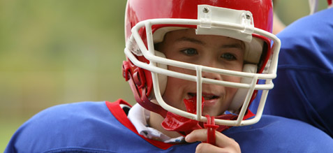 Pre-teen boy in a football uniform and helmet holding his mouth guard.