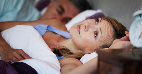 Woman lying awake in bed and staring at the ceiling.